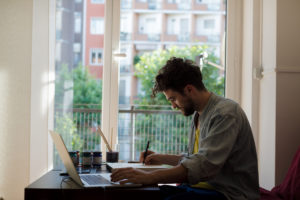 handsome hipster modern man working home using laptop